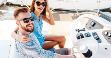 Starting their summer vacation. Top view of young couple looking at camera and smiling while driving yacht